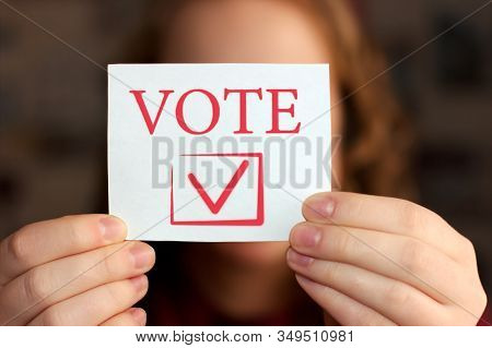 Vote Sign In Young Womans Hands The Concept Of Voting, Making Choices. Presidential And Parliamentar