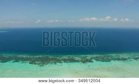Tropical Coral Atoll With Turquoise Water Against The Sky With Clouds Top View. Summer And Travel Va