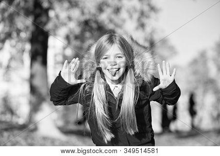 Girl Playful Grimace Face In Coat Enjoy Fall Park. Playful Kid Leisure. Child Blonde Long Hair Walki