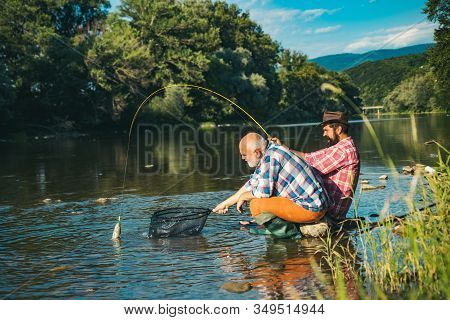 Mature Man With Adult Son Fishing. Fisher Masculine Hobby. Successful Fly Fishing. Cheerful Mature F