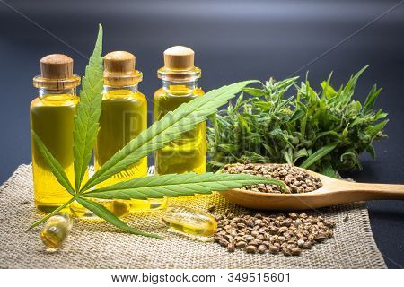Hemp Oil In A Glass Bottle Hemp Seeds In A Wooden Spoon And Hemp Leaf Placed On A Black Background T