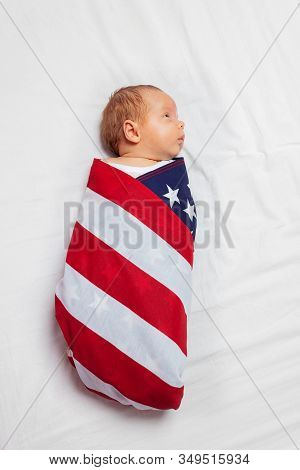 Portrait Of Little Calm Baby Infant Boy Wrapped In Us American Flag Laying On The Bed Sheet