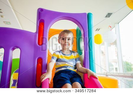 Little Boy Riding On Slide In Entertainment Center