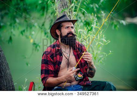 Portrait Man On Holiday. Fisherman Fishing Equipment. Set Up Rod With Hook Line Sinker. Bearded Eleg