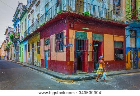 Havana, Cuba, July 2019, Woman Walking By A Food Store At The Corner Of Calle Muralla & Cuba In The