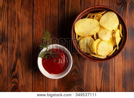 Wavy, Potato Chips In A Plate With Ketchup On A Wooden Table. Top View Of Snacks. Stock Photo Potato
