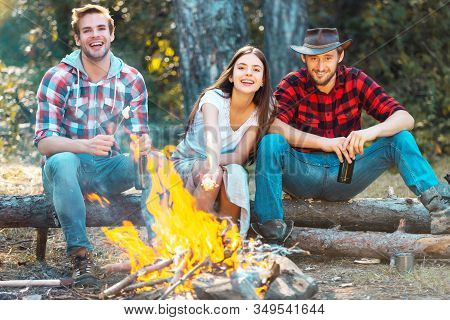 Friends Hikers Watching Fire Together On Camp. Company Friends Picnic Or Barbecue Near Bonfire. Frie