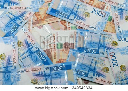 Russian Banknotes Of 5000 And 2000 Rubles Are Scattered Chaotically. Background Made Of Money.