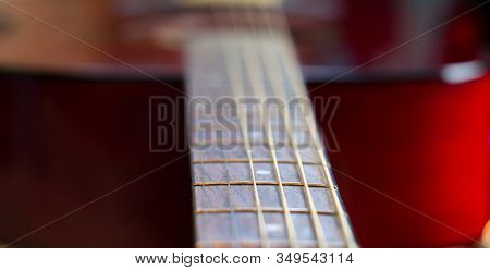 Cherry-colored Acoustic Guitar Close-up. Vulture And Strings.  Frets Guitar