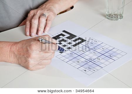 Portrait of mature woman playing sudoku puzzle.