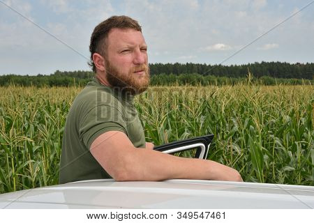 Farmer Near The Corn Field In Summer. A Man On A Background Of A Field With A Corn Car White. A Man