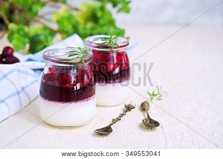 Dessert, Creamy Panna Cotta With Cherry Sauce In In Vintage Glass Jars On A Light Concrete Backgroun