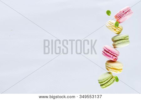 Classic Colorful Macarons. Six Pink, Yellow And Green Macaron Cookies Top View Copy Space