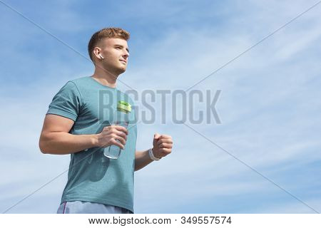 Athletic Slim Handsome Guy Runner Young Beautiful Man With Bottle Of Water Listening To Music In Wir