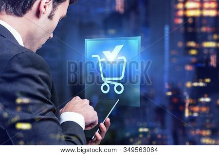 Side View Of Businessman Using Smartphone In Blurry Night City With Double Exposure Of Online Shoppi
