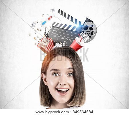 Happy Astonished Blonde Teen Girl In Standing Over Concrete Background With Clapper Board And Cinema
