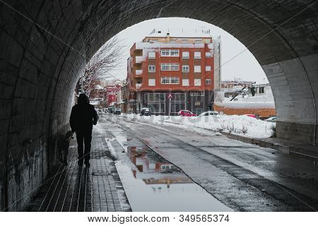 Man With His Labrador Dog Walking Through A Snowy City Tunnel. Winter And Lifestyle Concept