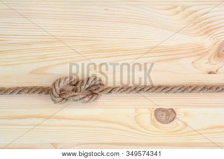 Marine Knot Used In Yachting, Figure Eight Knot. Nautical Knot On Wooden Background.