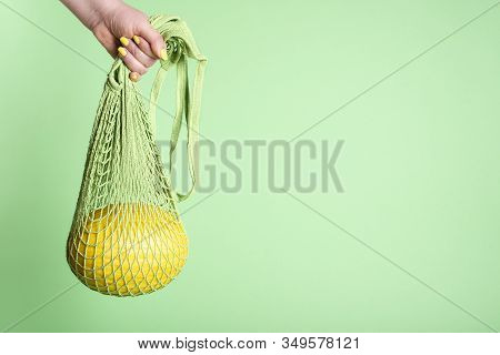 Buying Yellow Melon. Woman Hand Holding A Shopping Bag With Melon On Green Background. Summer Fruit