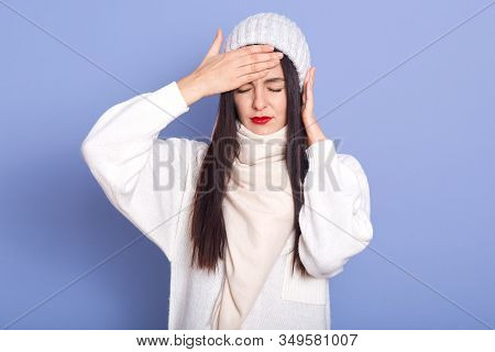 Horizontal Indoor Picture Of Exhausted Ill Sweet Young Lady Closing Eyes, Putting Hand On Forehead,