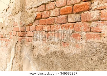 Peeled Plaster On An Old Brick Wall. Broken Wall. Red Bricks In Old Wall. Detail Of Wall.
