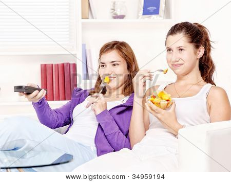 Teenage Girls Watching Tv And Eating Fruit Salad