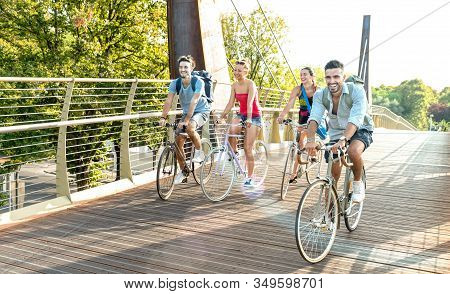 Happy Millenial Friends Having Fun Riding Bike At City Park - Friendship Concept With Young Millenni