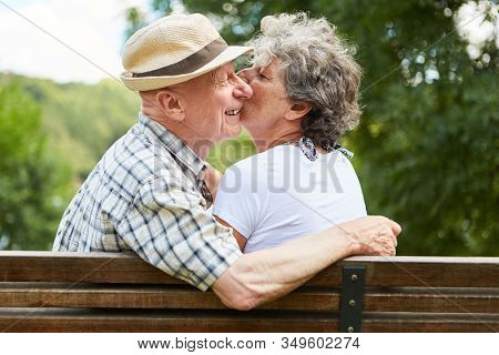 In love seniors dating in the park in the summer give a kiss