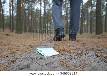 Young Man Loses His Euro Money Bills On Russian Autumn Fir Wood Path. Carelessness And Losing Money