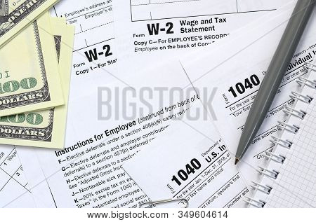 The Pen, Notebook And Dollar Bills Is Lies On The Tax Form 1040 U.s. Individual Income Tax Return. T