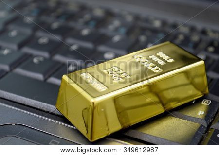 Closeup Of A 200 Gram Bar Of Pure Gold Sitting On A Laptop To Illustrate The Ease Of Online Trading