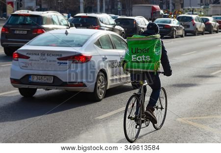 Bucharest, Romania - January 07, 2020: An Uber Eats Food Delivery Courier Delivers Food In Bucharest