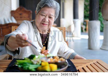 Old Elderly Senior Elder Woman Eating Food. Mature Retirement Lifestyle