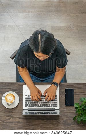 Overhead View Photo Of Asian Woman Typing Laptop At Coffeeshop