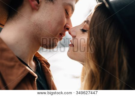 Heterosexual Young Couple In Love Kisses On The Street. Stylish Hipster Guys Enjoy Life.