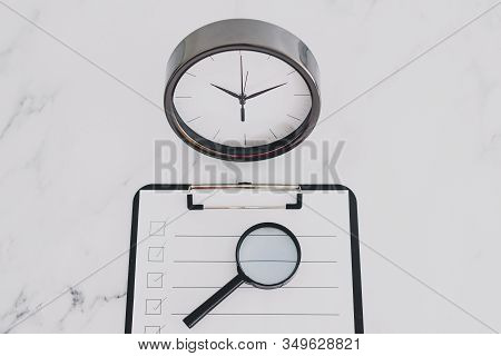 Productivity And Deadlines, To Do List On Clipboard Next To Big Clock On Business Desk
