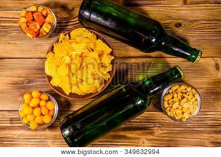 Two Bottles Of Beer And Different Snacks On Rustic Wooden Table. Top View