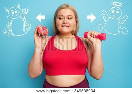 Fat Girl Thinks To Eat Donuts Instead Of Does Gym. Concept Of Indecision And Doubt With Angel And De