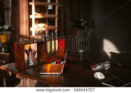 Photographers Workplace In Loft Style Studio. A Mirrorless Digital Camera On Gimbal Stabiliser, An U