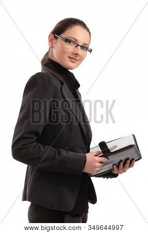 Attractive young businesswoman reading personal organizer, looking at camera, smiling. Isolated on white.