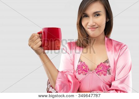 Asian Women In Sleepwear And Pink Silk Robe Drinking Milk In A Red Glass Before Going To Bed. Lady I