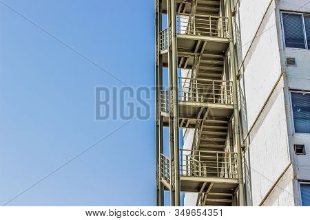Metal Fire Escape Stairs Construction Outdoor Side Of High Building And Empty Blue Sky, Copy Space F