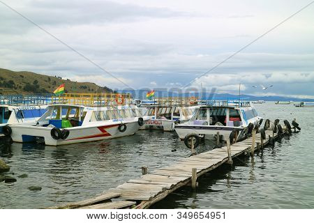 Empty Wooden Dock Surrounded By Boats On Lake Titicaca, The Town Of Copacabana, Bolivia, South Ameri