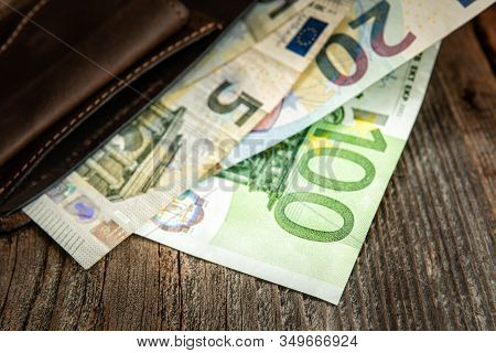 Brown Leather Wallet With Euros On An Old Wooden Surface. Close Up.