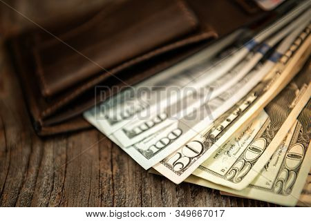 Brown Leather Wallet With Dollars On An Old Wooden Surface. Close Up.