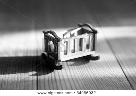 Empty Crib On A Wooden Background Infertility Concept, Lack Of Children In The Family, Empty Crib