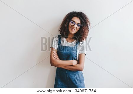 Smiling Young Woman In Glasses With Dark-brown Hair Posing With Arms Crossed In Front Of Light Wall.