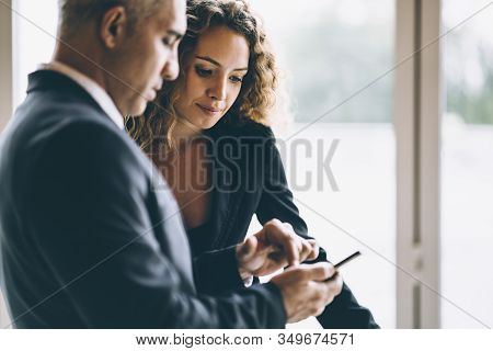 Scene Of Business Woman Looking At The Cellphone Of Her Colleague Or Her Boss While The Man Point Fi