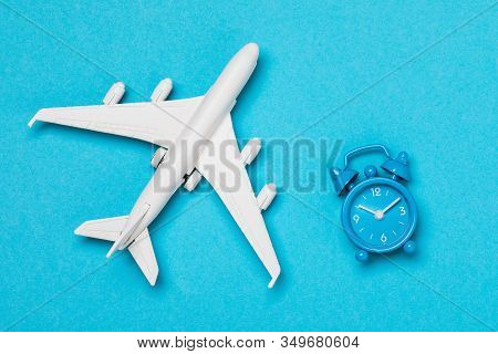Airplane And Clock On A Blue Background, Top View. The Concept Of The Duration Of Flights