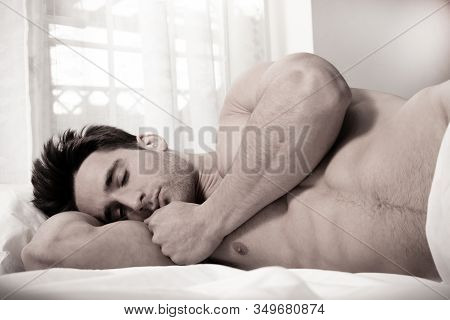 Handsome Naked Muscular Man With Beard Sixpack Abs Lying In Bed Covered With Sheet